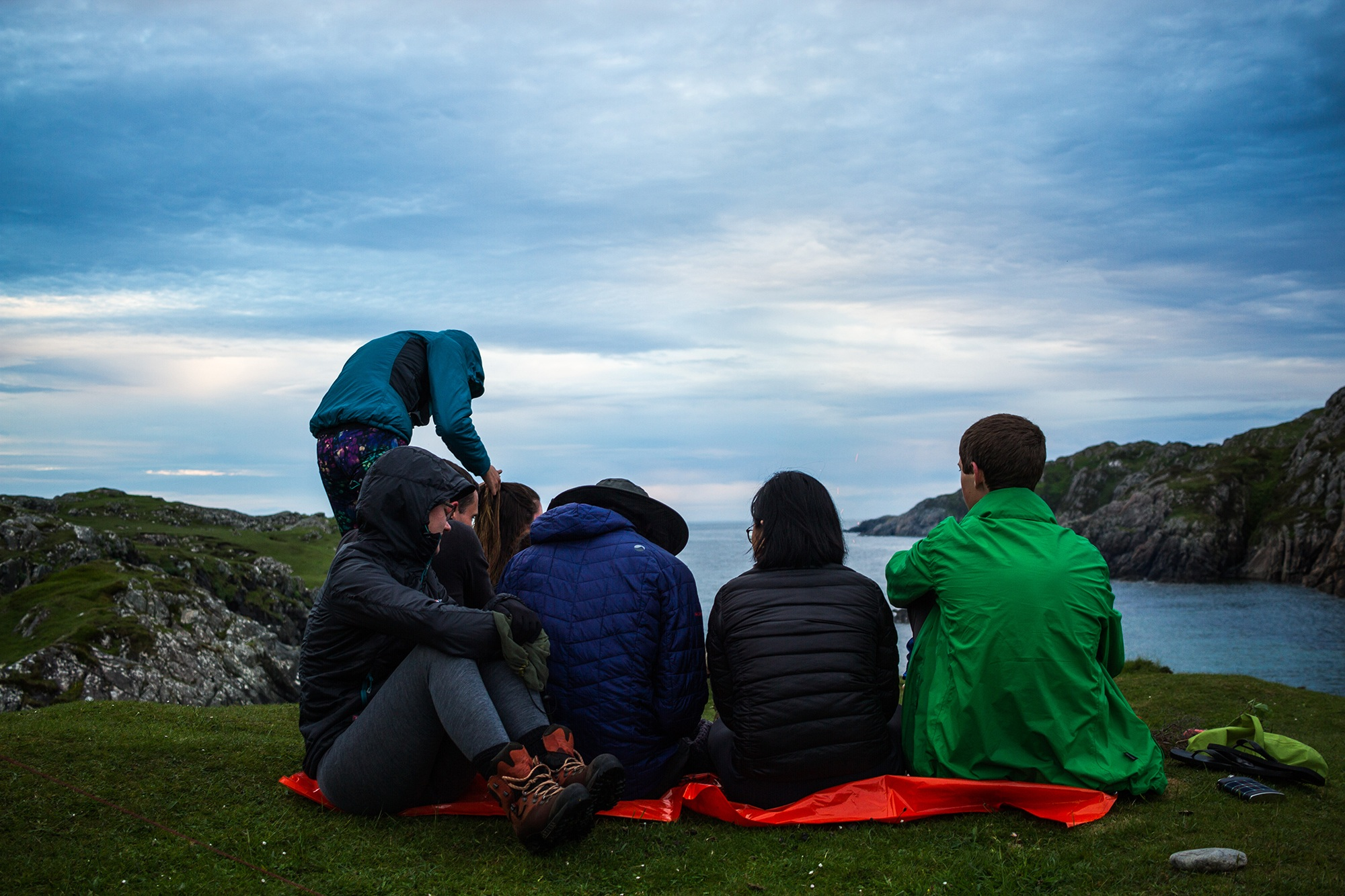 Photograph of Group sat in a hidden cove, Assynt, shot by Jessie Leong