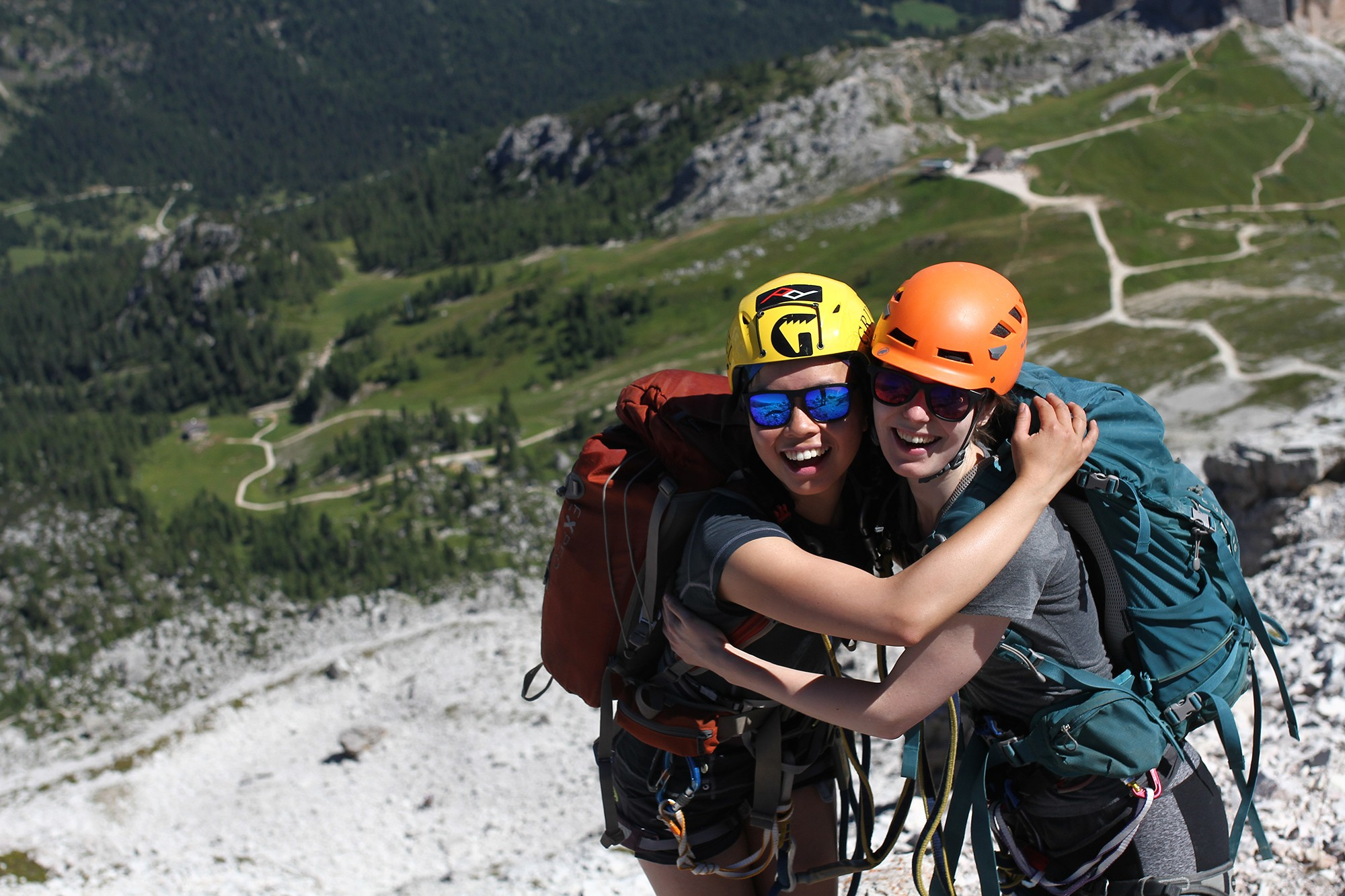 Jessie leong and Emma Bryning hug at the top of Averau, a via ferrata route in The Dolomites