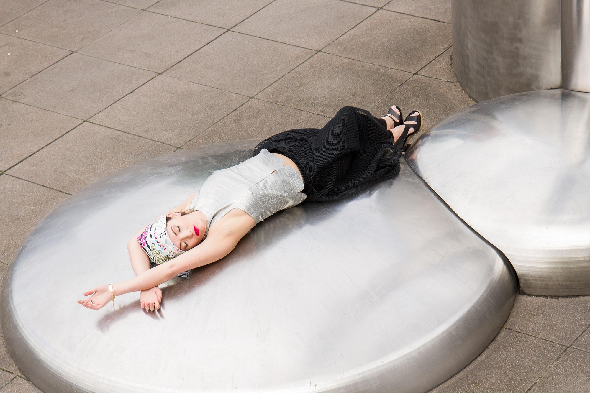 Model lying down wearing Lavinia Cadar Scarf as a headscarf